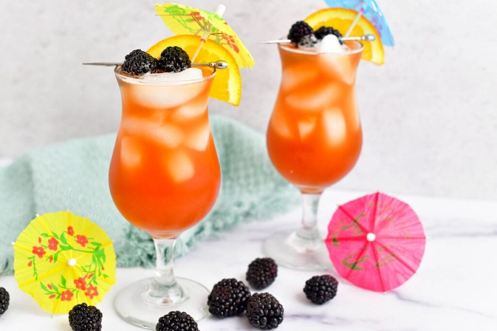 Two hurricane glasses are filled with orange rum runner and garnished with fruit and umbrellas.