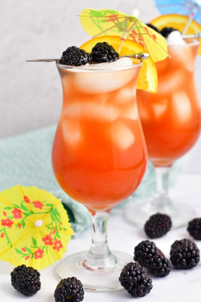 A handful of blackberries are scattered around two rum runners.