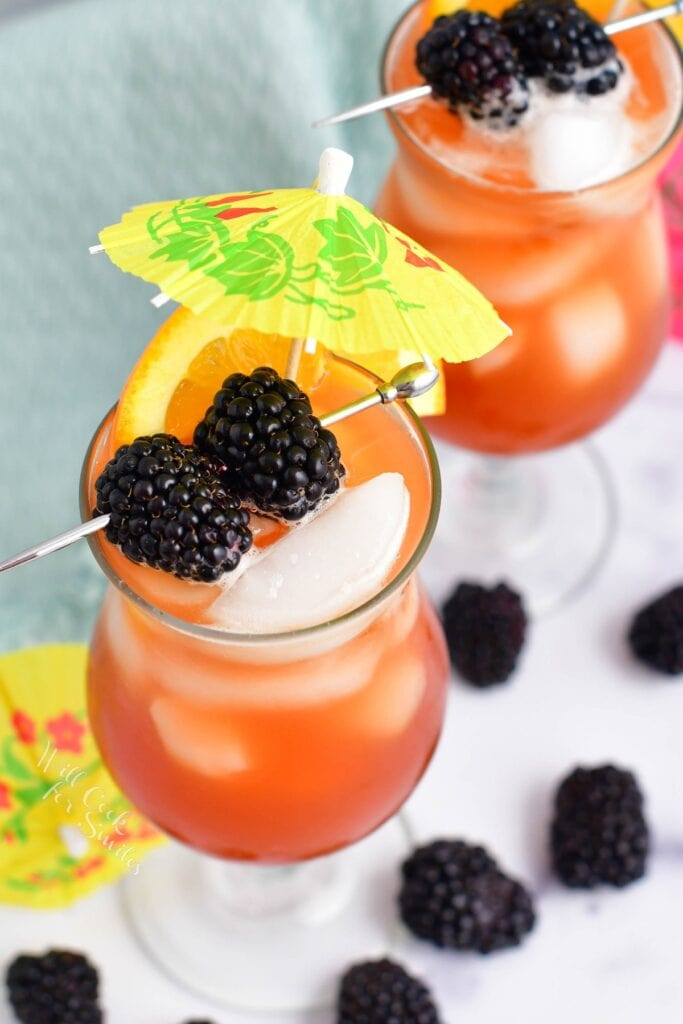 Two rum runners are in cocktail glasses and garnished with mini umbrellas and blackberries.