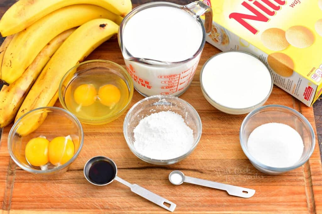 The ingredients for banana pudding are placed on a wooden surface.