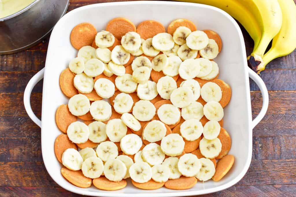 Nilla wafers and bananas are lining the bottom of a white dish.