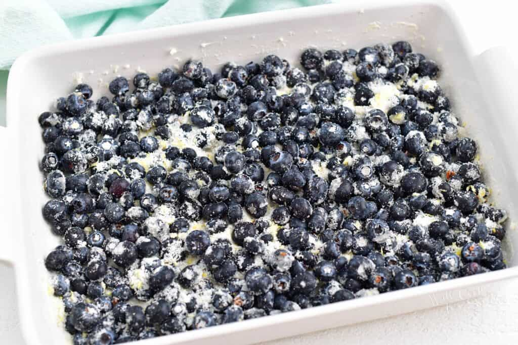 Blueberries and sugar are mixed together and spread evenly in a large white casserole dish.