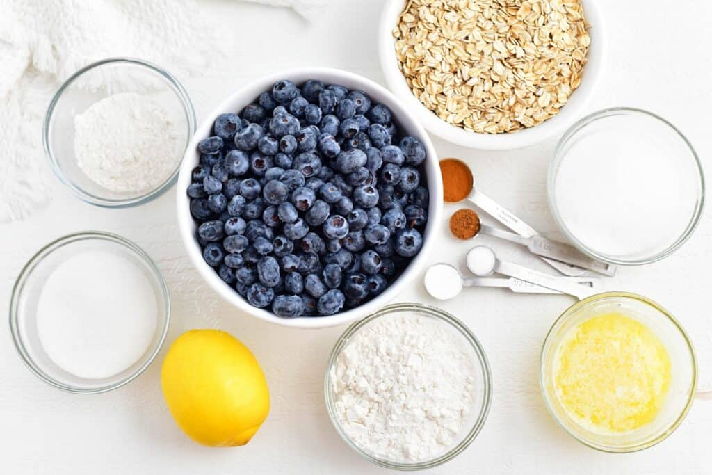 The ingredients for blueberry crisp are placed on a white surface.