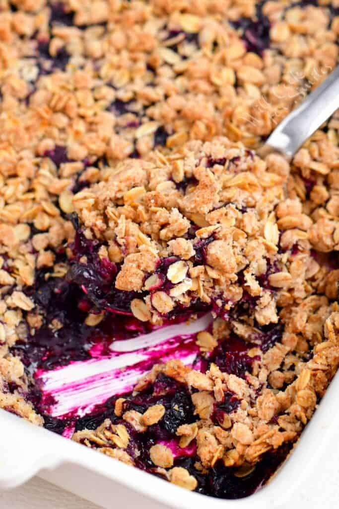 A scoop of blueberry crisp is being lifted from the casserole dish.