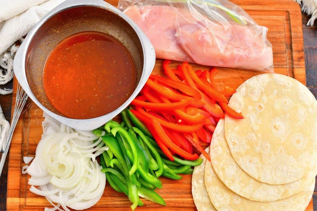 The ingredients for chicken fajitas are spread out on a wooden cutting board.