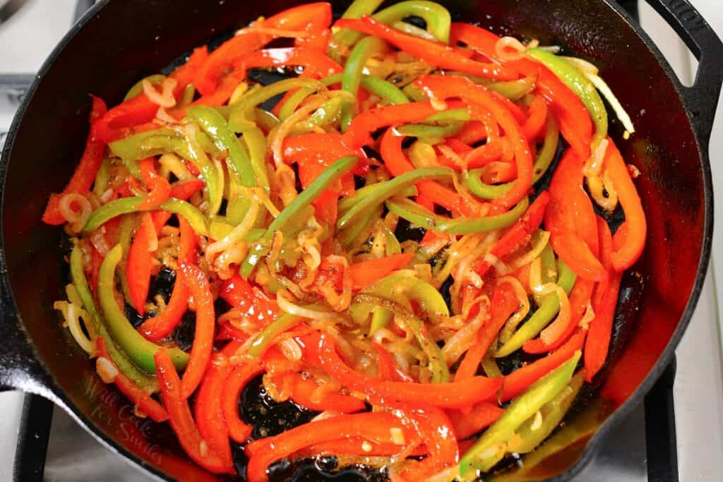 Peppers and onions are cooked in the marinade.