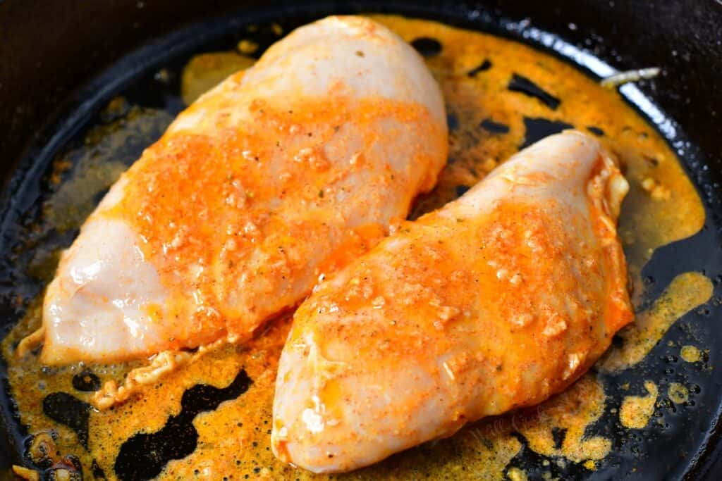Uncooked chicken is doused with marinade in a black skillet.