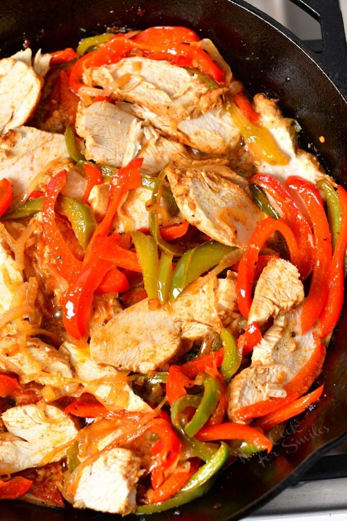 Chicken and veggies are mixed in the same skillet.