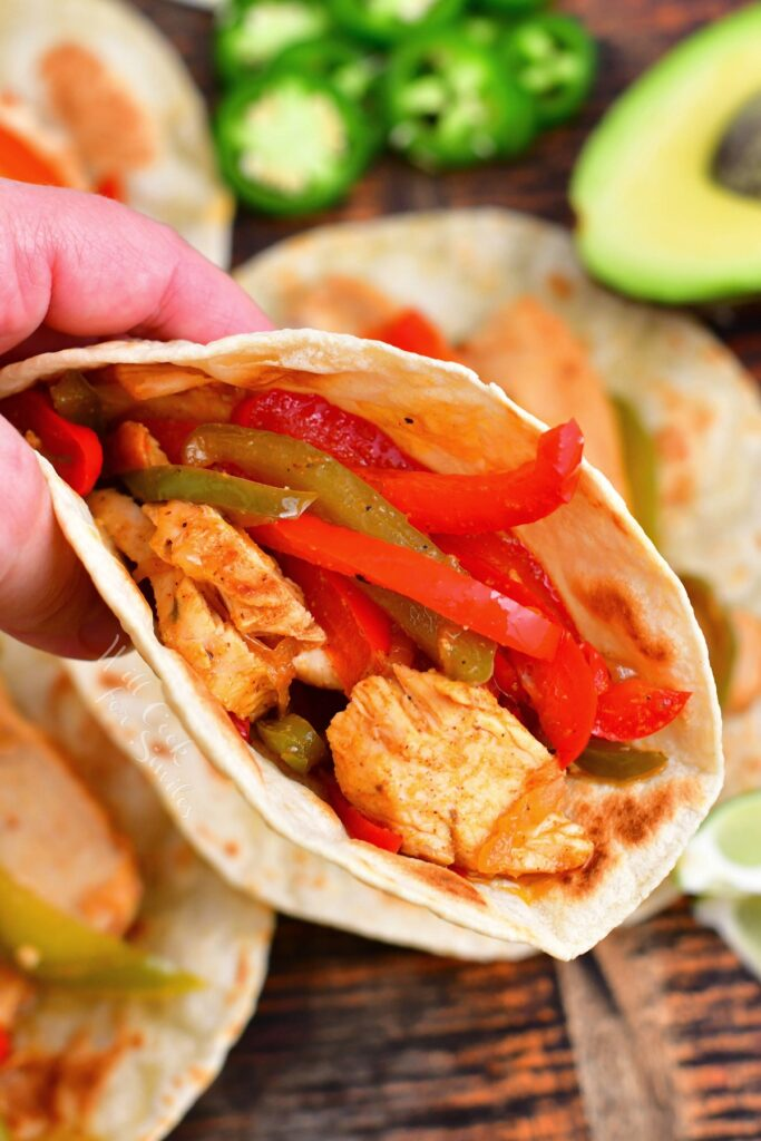 A hand is holding up a perfectly made chicken fajita.