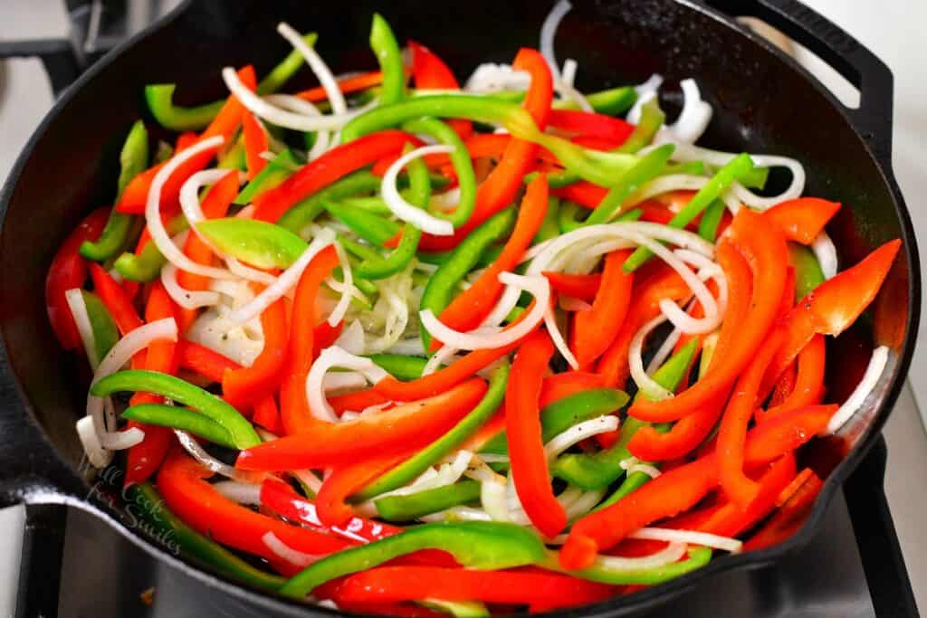 Uncooked veggies are in a large black skillet.