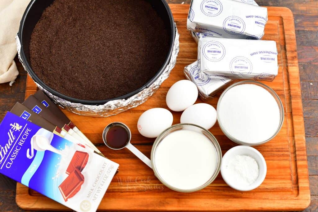 The ingredients for chocolate cheesecake are presented on a wooden surface.