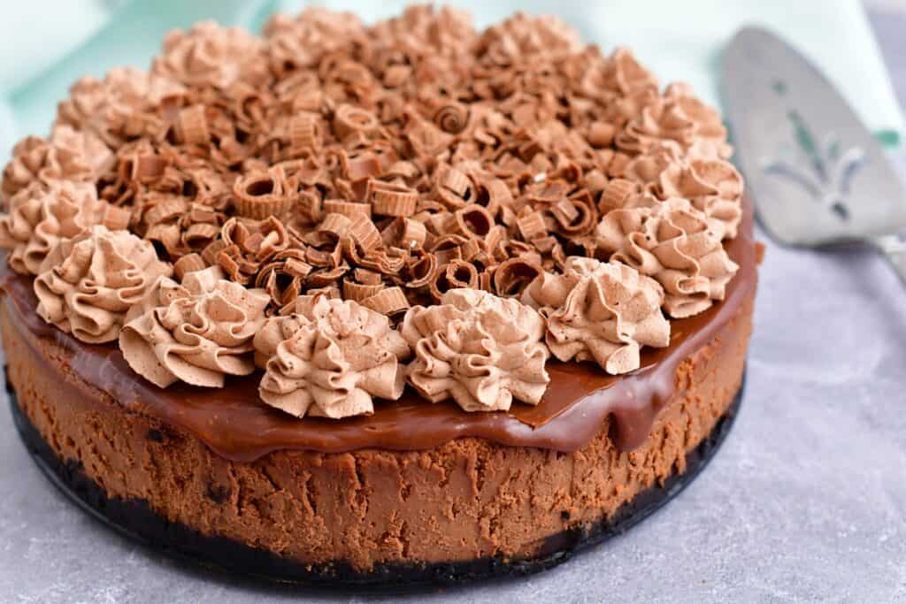 A chocolate cheesecake is covered with whipped cream and shaved chocolate.