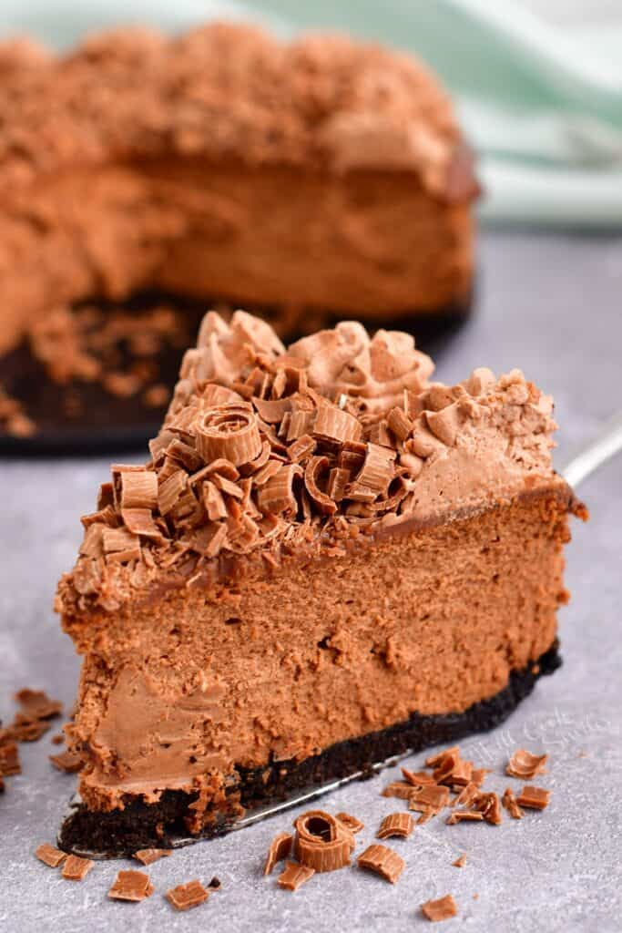 A slice of chocolate cheesecake is read to be eaten.