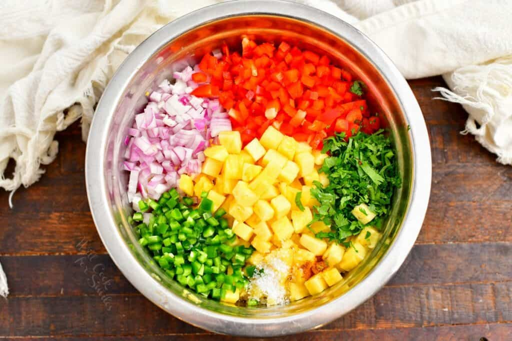 The ingredients for fresh pineapple salsa are placed in a large silver bowl.