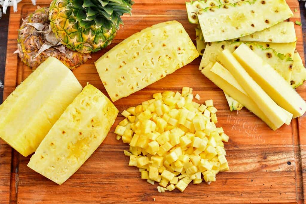 The ingredients for pineapple salsa are placed on a wooden cutting board.