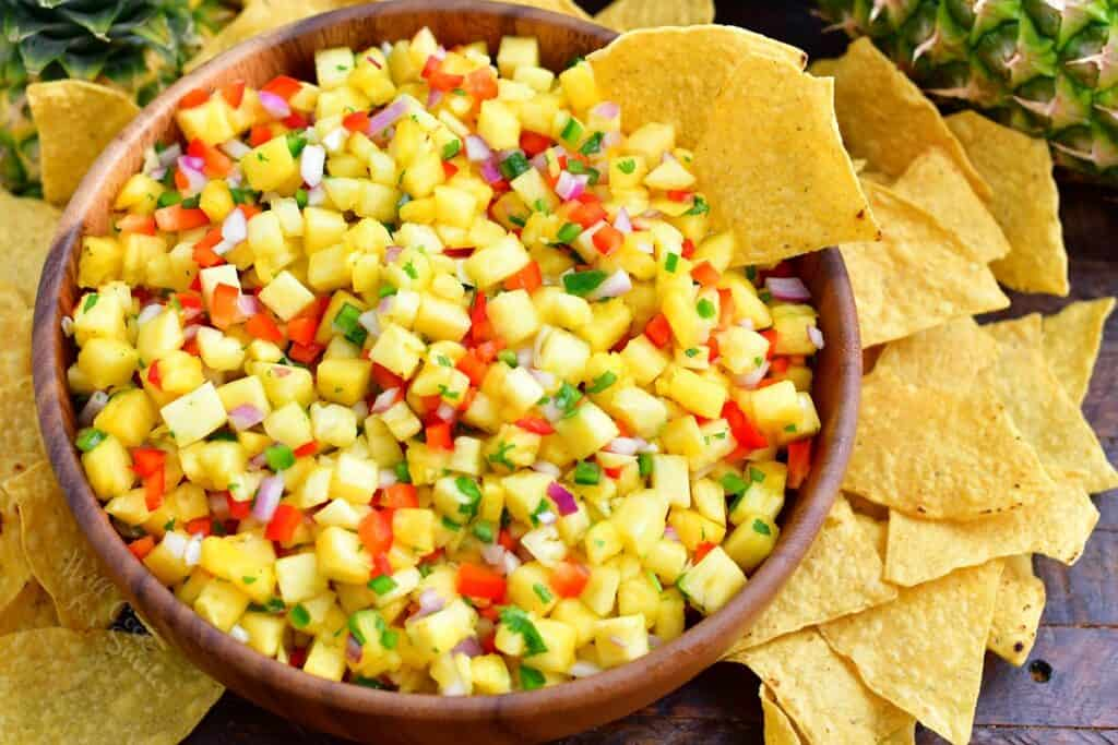Chips are served alongside pineapple salsa.