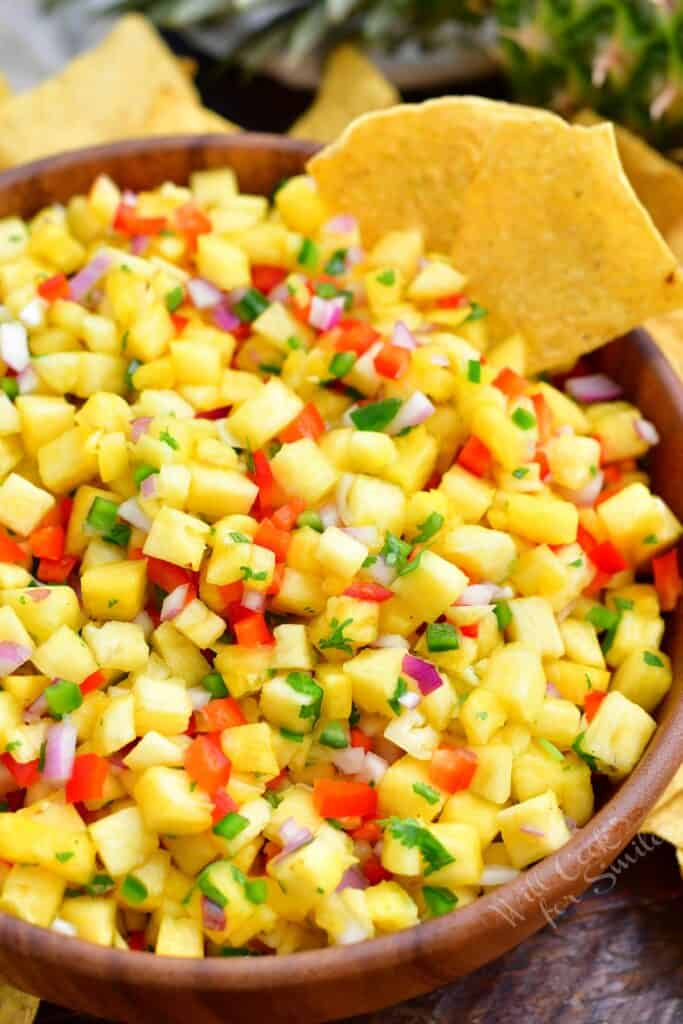 Chips are placed on the side of a bowl filled with pineapple salsa.