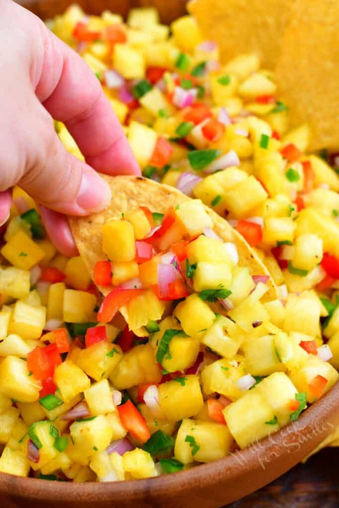 A chip is dipped into pineapple salsa.