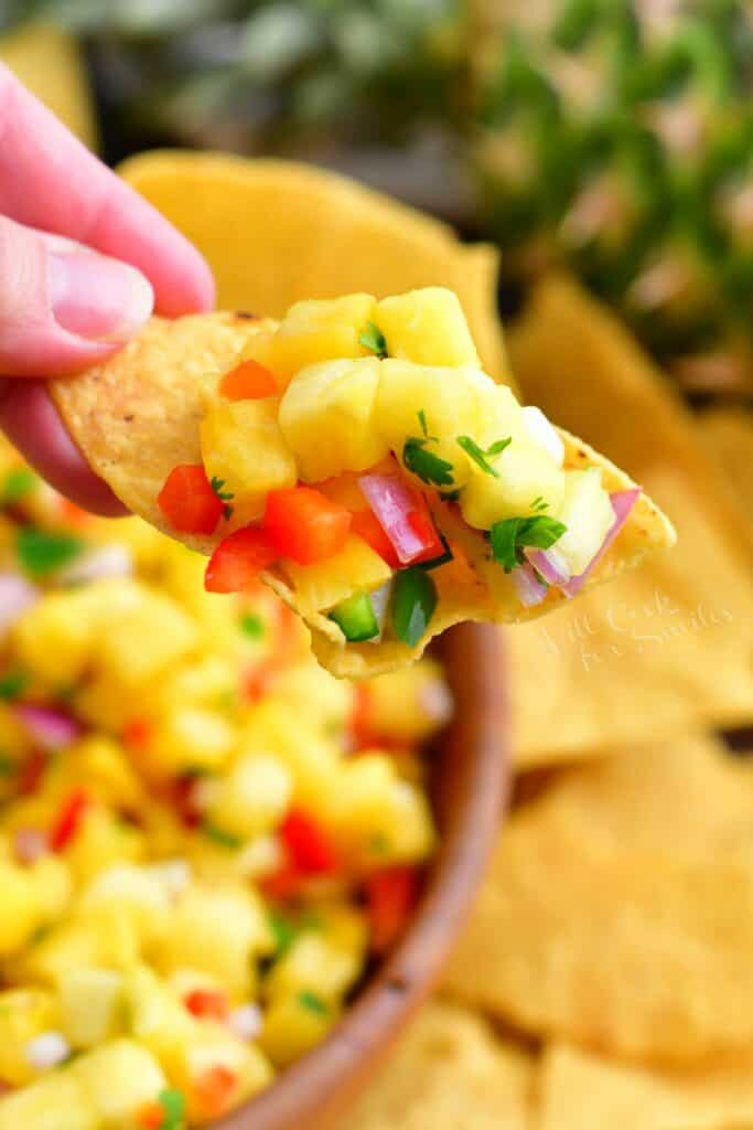 A tortilla chip is topped with salsa.