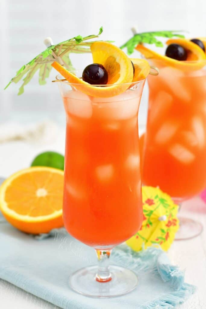 A tall glass of rum runner is garnished with fruits and small palm trees.