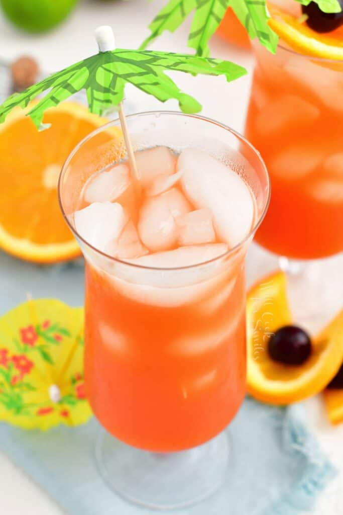 A glass of rum punch is garnished with a small paper palm tree.