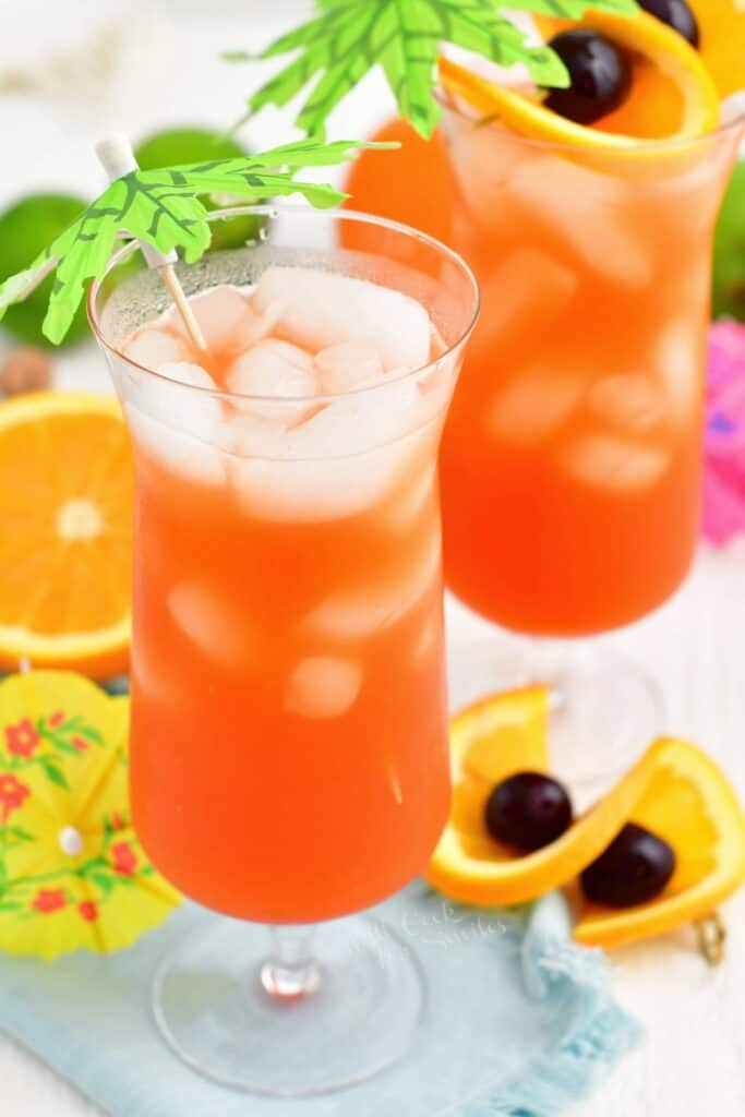 Ice cubes have floated to the top of a glass filled with rum punch.
