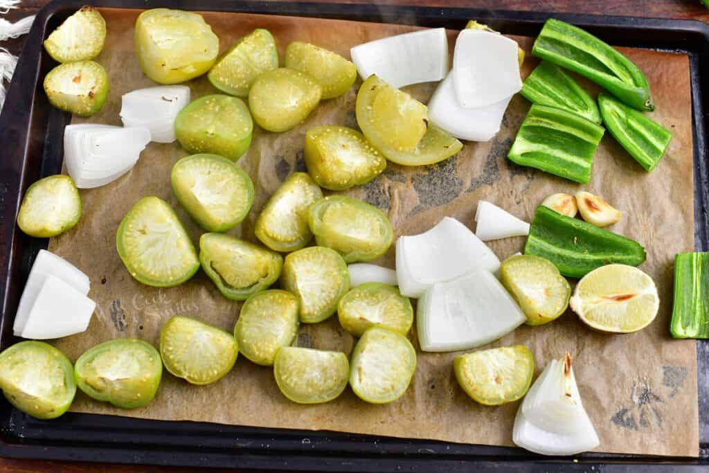 The ingredients for salsa verde are spread out on a baking sheet and have been cooked.