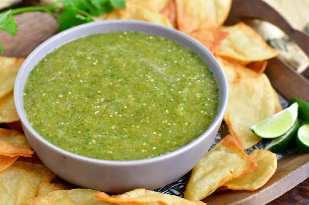 A bowl of green salsa is surrounded by chips.