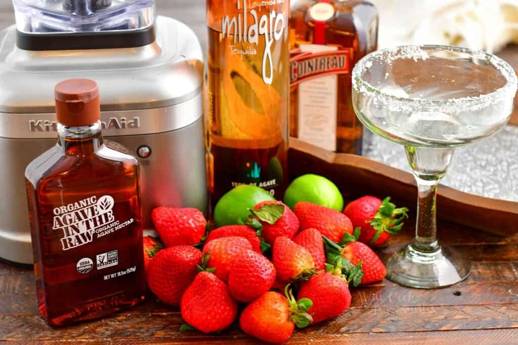 The ingredients for strawberry margaritas are laid out on a wooden surface.
