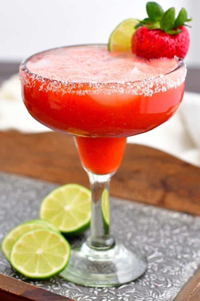 Slices of lime are next to a tall glass of strawberry margarita.
