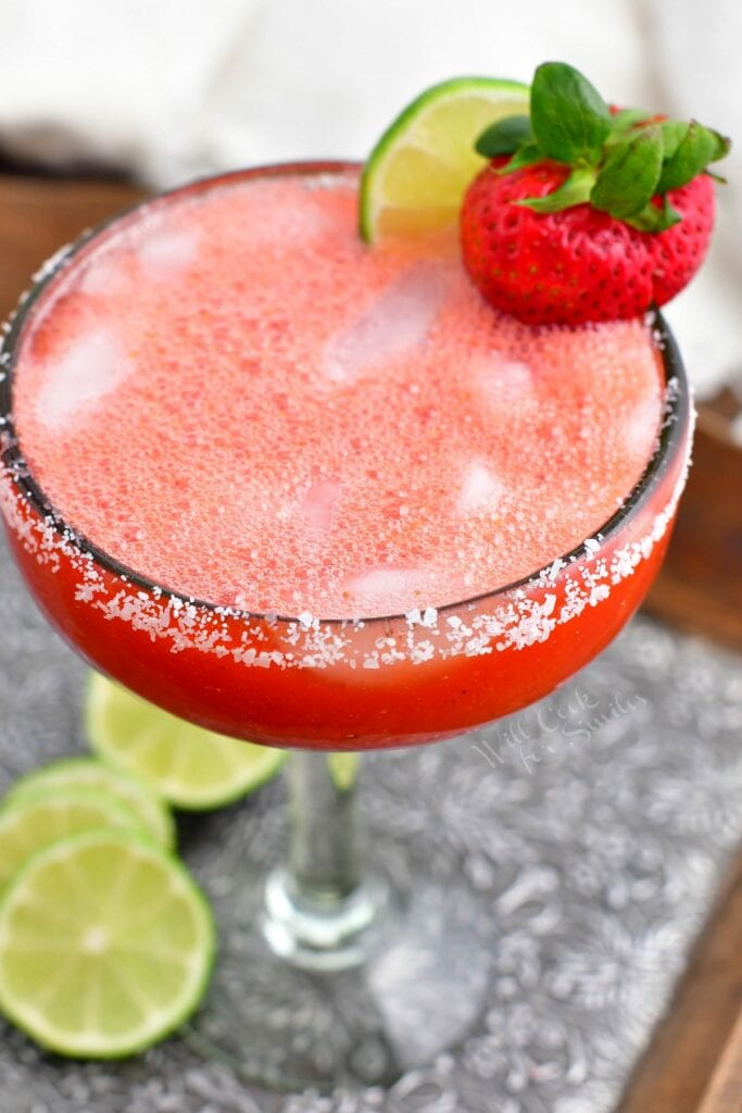 A strawberry and lime slice garnish a glass of strawberry margarita.