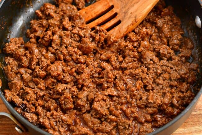 Cooked ground beef is in a large skillet.