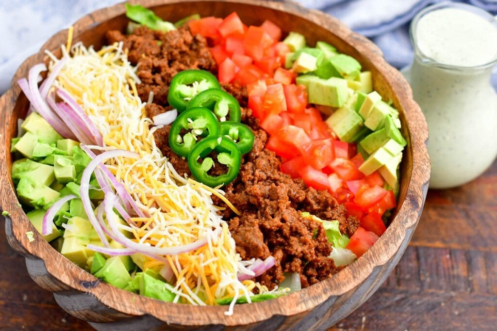 All of the ingredients for taco salad are lined up in a bowl.