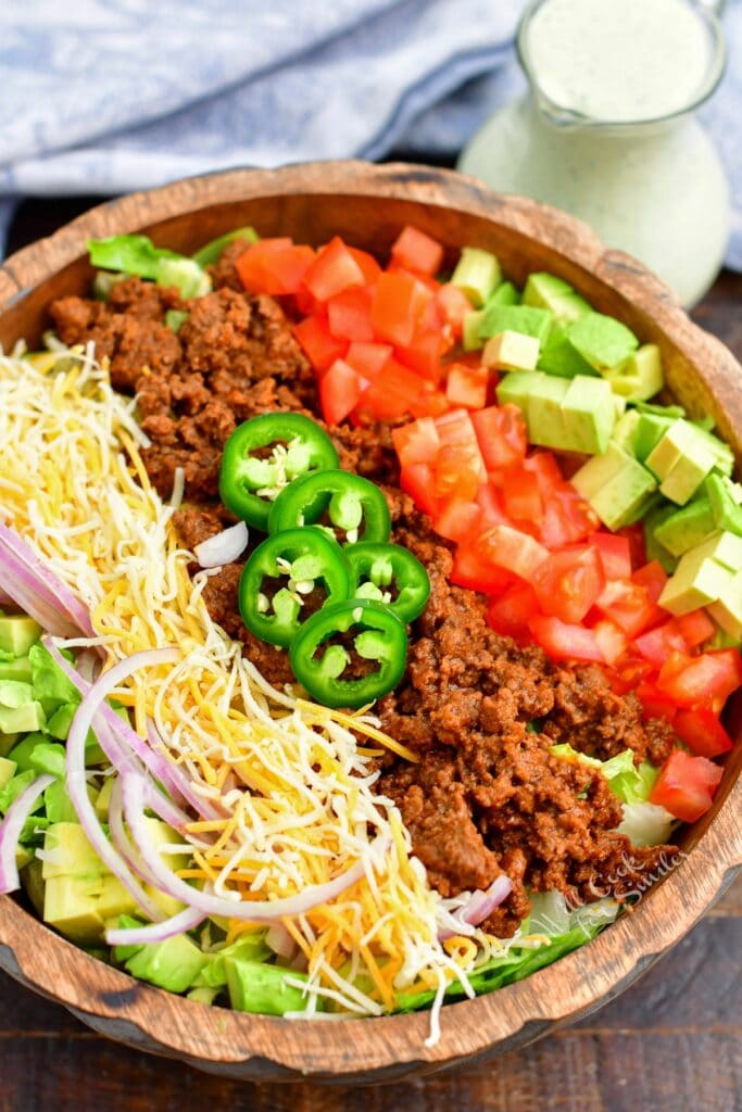 A taco salad that has not yet been tossed is in a large bowl.