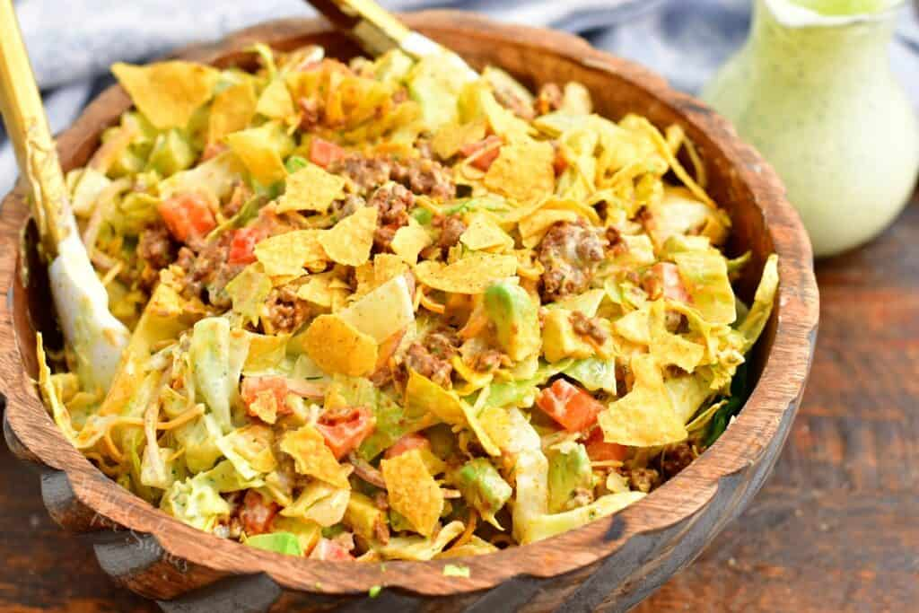 A taco salad is tossed in a wooden bowl.