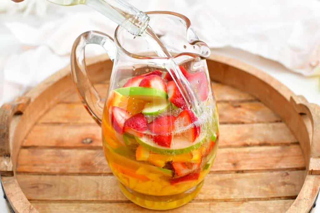 Clear liquid is being added to a pitcher of fruit.