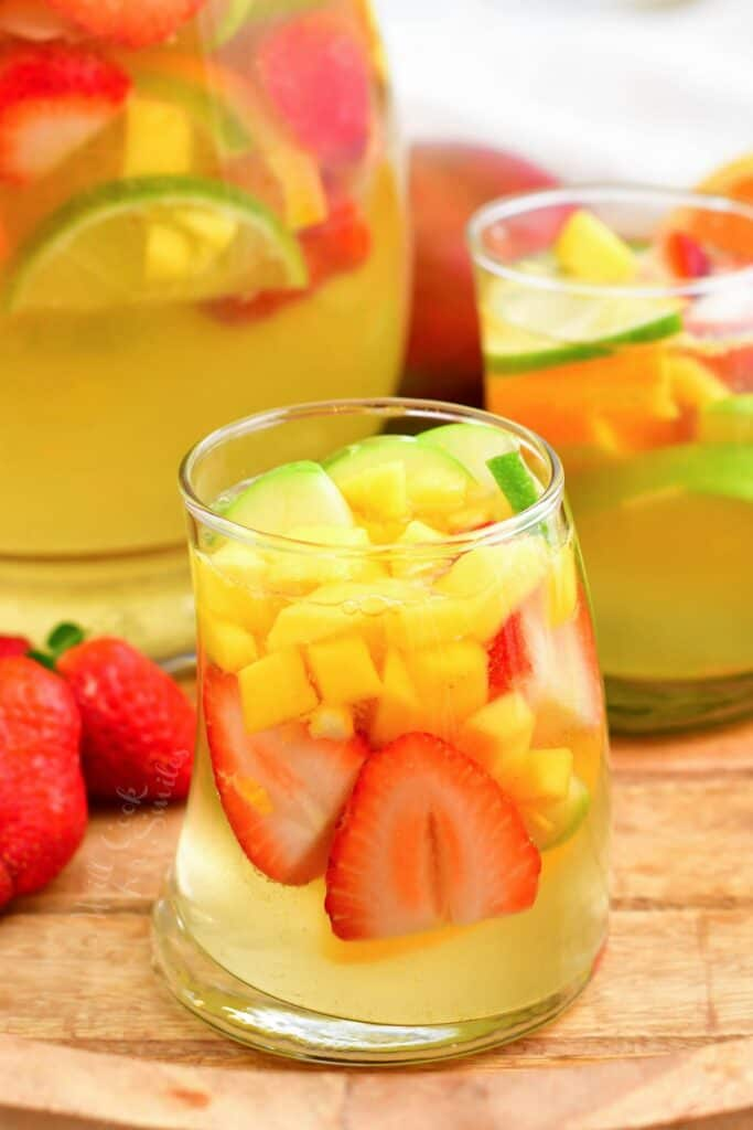 Two glasses of white sangria are placed next to a full pitcher.