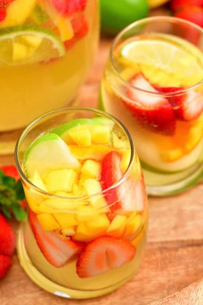 Two glasses are filled with fruit and white sangria.
