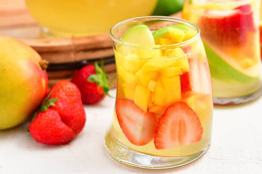Strawberries and mangoes are in a glass willed with sangria.