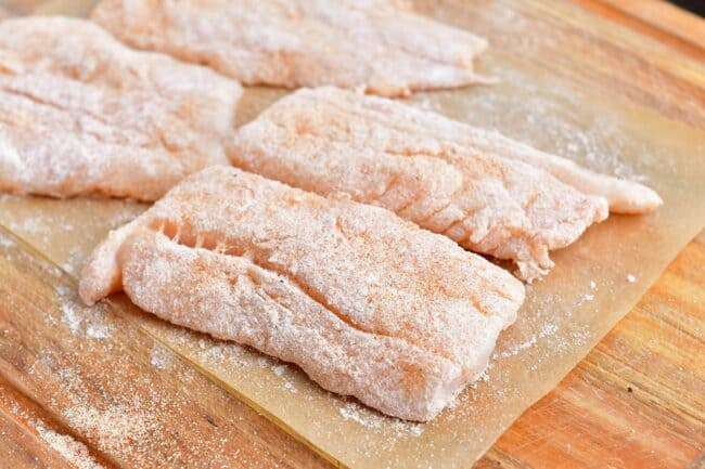 Uncooked cod is coated in flour and placed on a sheet of parchment paper.