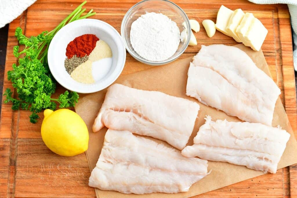 The ingredients for baked cod are placed on a wooden cutting board.