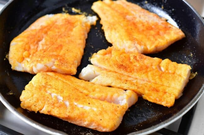 Cod is being seared in a large skillet.