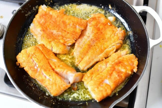 Filets are being cooked in a buttery sauce in the skillet.