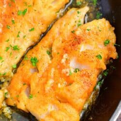 Cod fillets are fully cooked in a large black skillet.