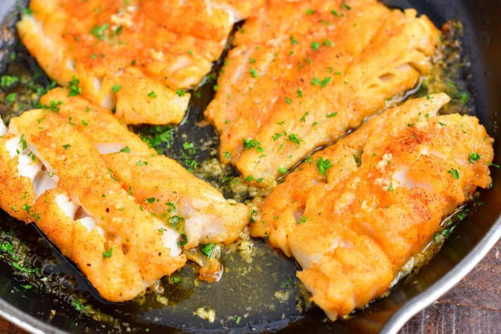 Parsley is garnishing cod filets.