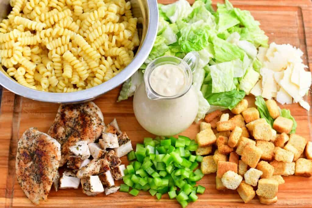 The ingredients for chicken caesar pasta salad are placed on a wooden surface.