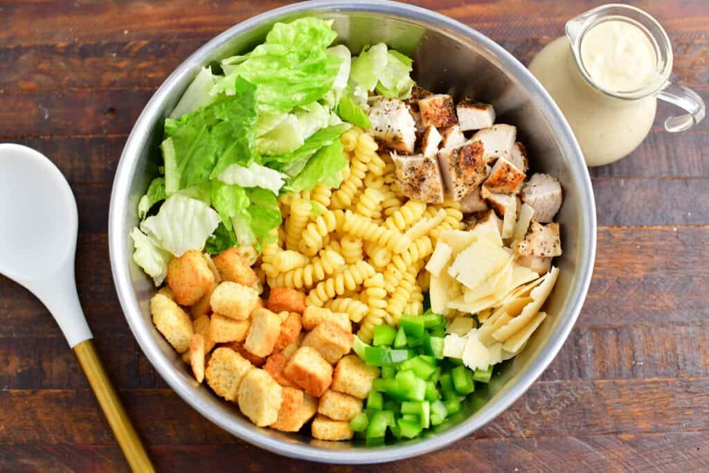 All of the ingredients for the pasta salad are in a large bowl.