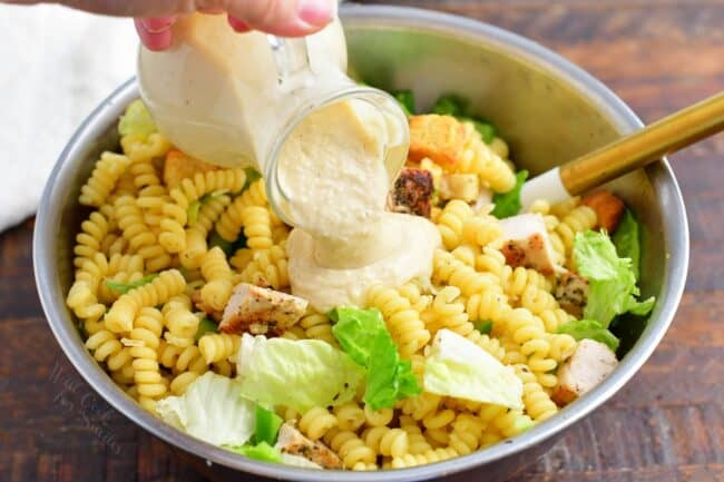 Dressing is being poured on top of pasta salad.