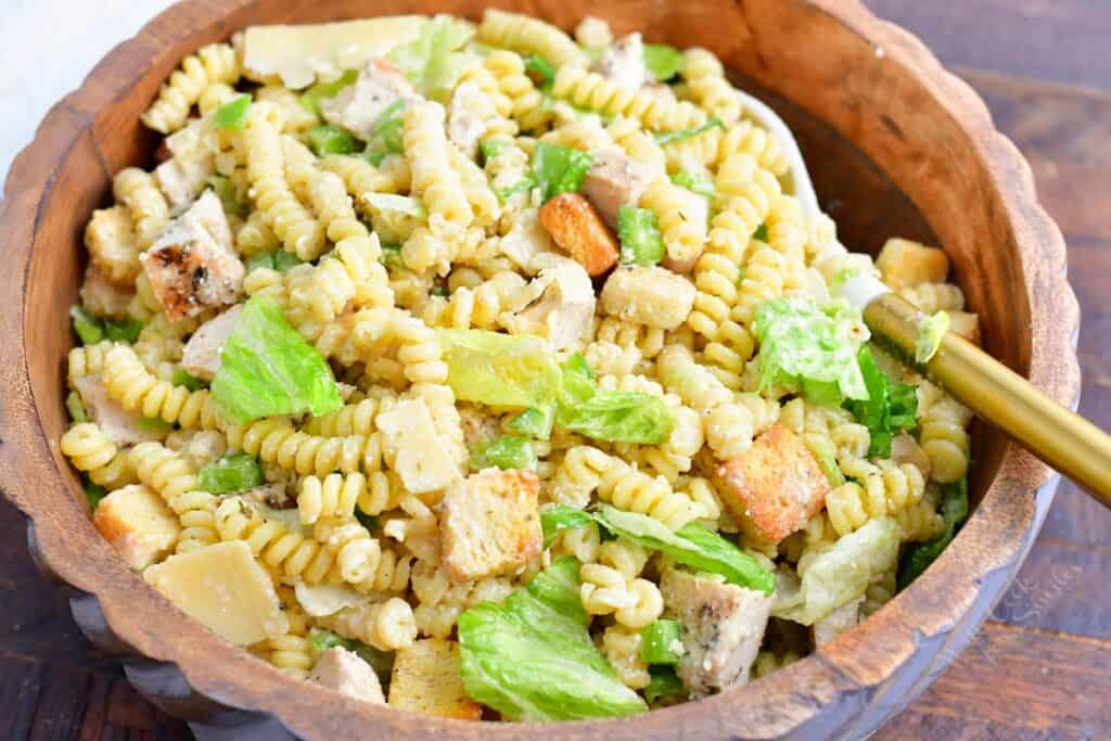 The tossed pasta salad is presented in a large wooden bowl.