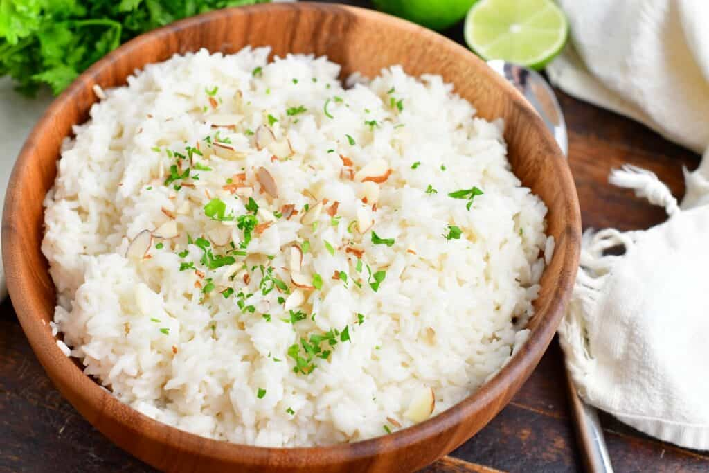 Coconut rice is presented in a wooden bowl and garnished with almonds and fresh herbs.